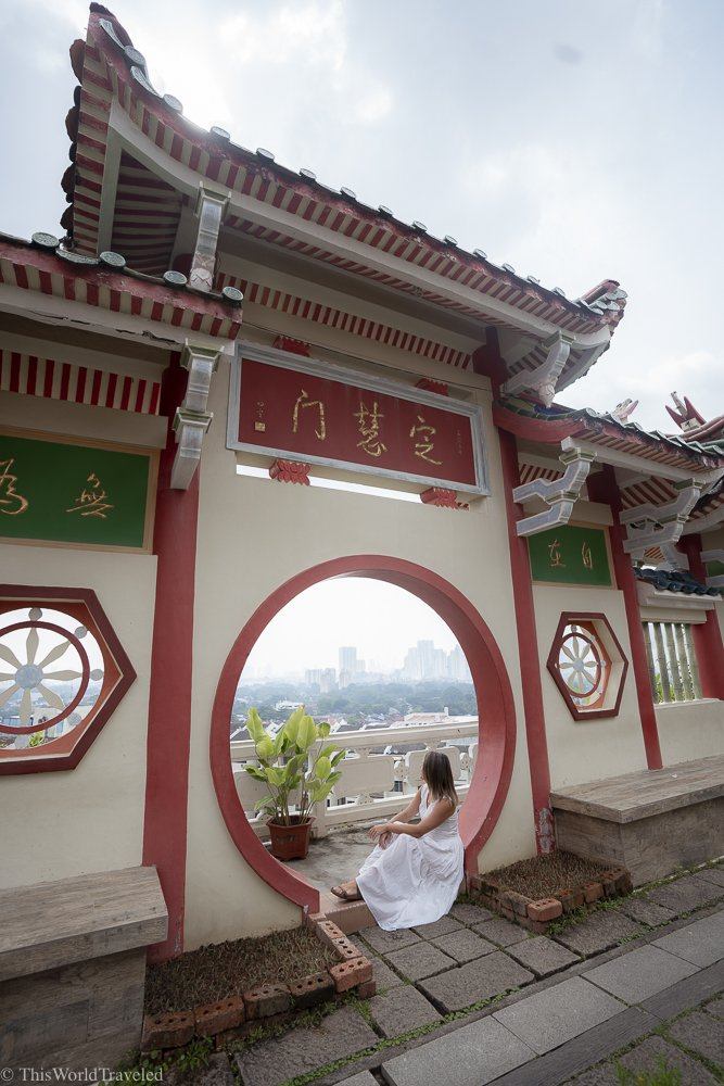 Girl sitting inside a window in a large temple in Penang