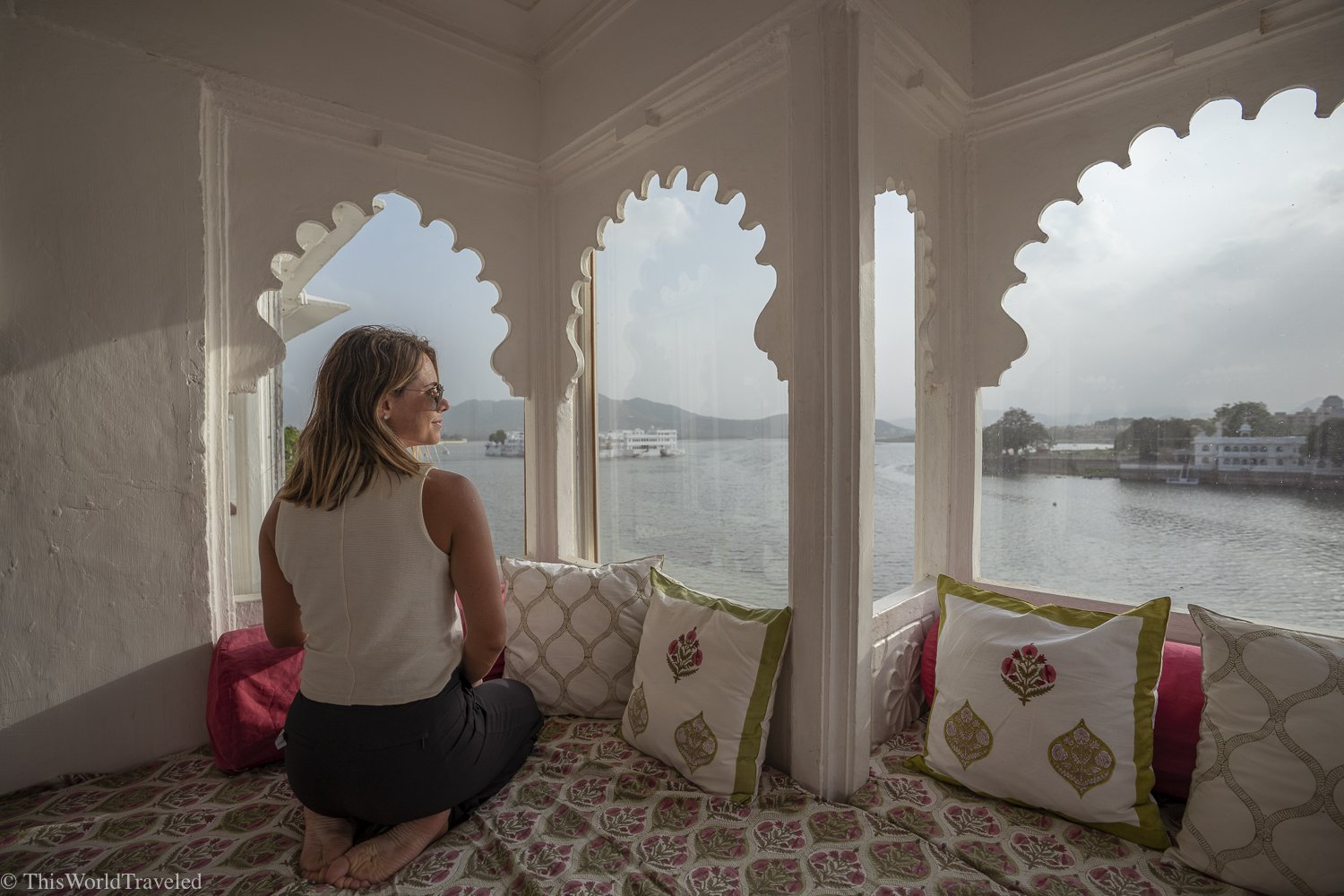 girl sitting on cushions looking out through white windows to the view of the lake