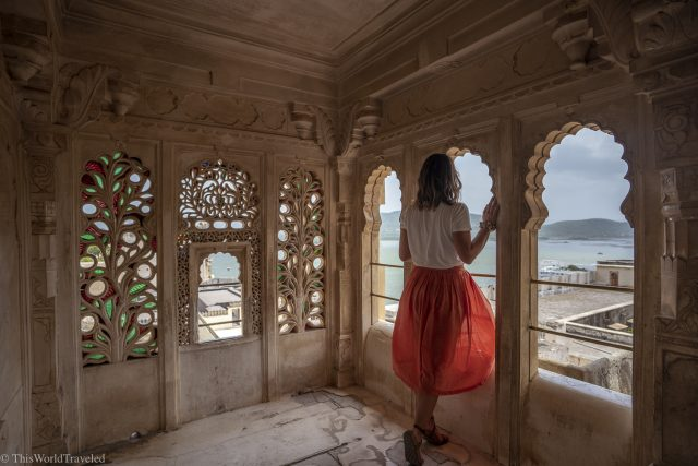 Girl in orange skirt standing in an archway in Udaipur's city palace overlooking a large lake