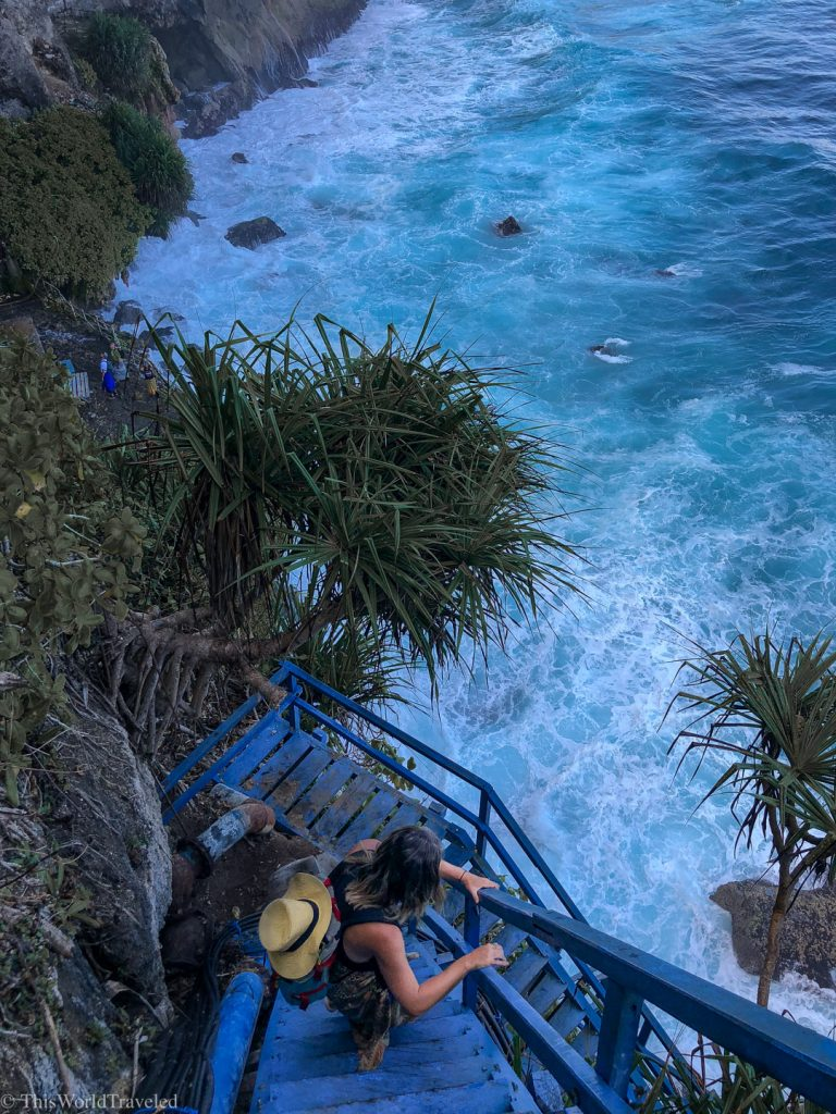 A girl climbing down blue stairs on the coast of Nusa penida