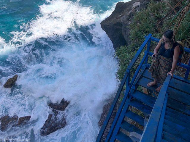 Girl walking down steep metal blue stairs in Nusa Penida