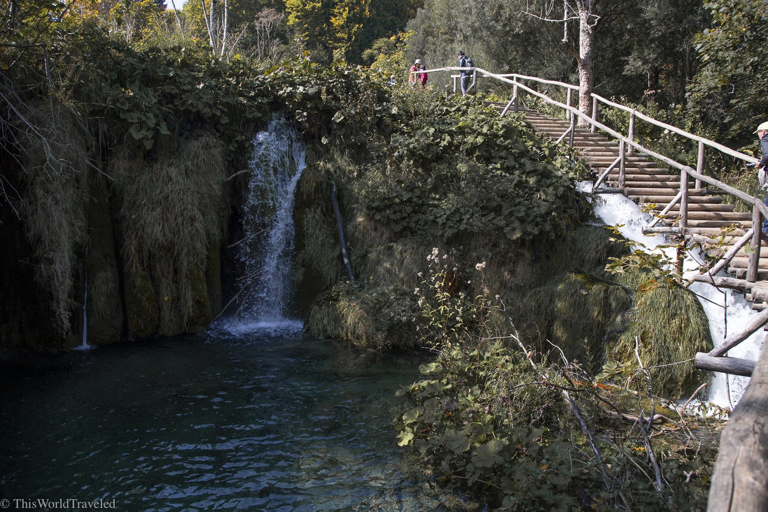A waterfall in Plitvice Lakes National Park surrounded by green trees and a boardwalk