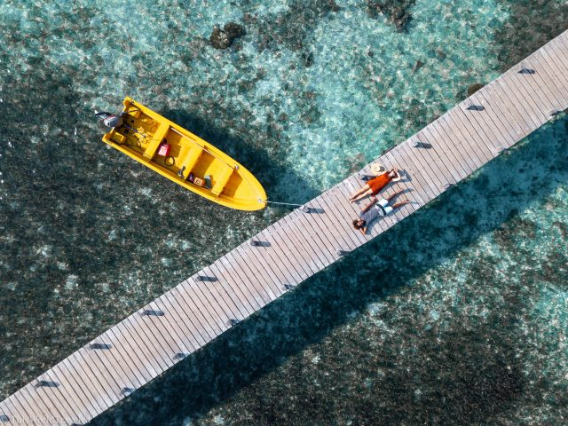 Couple laying on the dock at Kanawa Island in the Komodo Islands