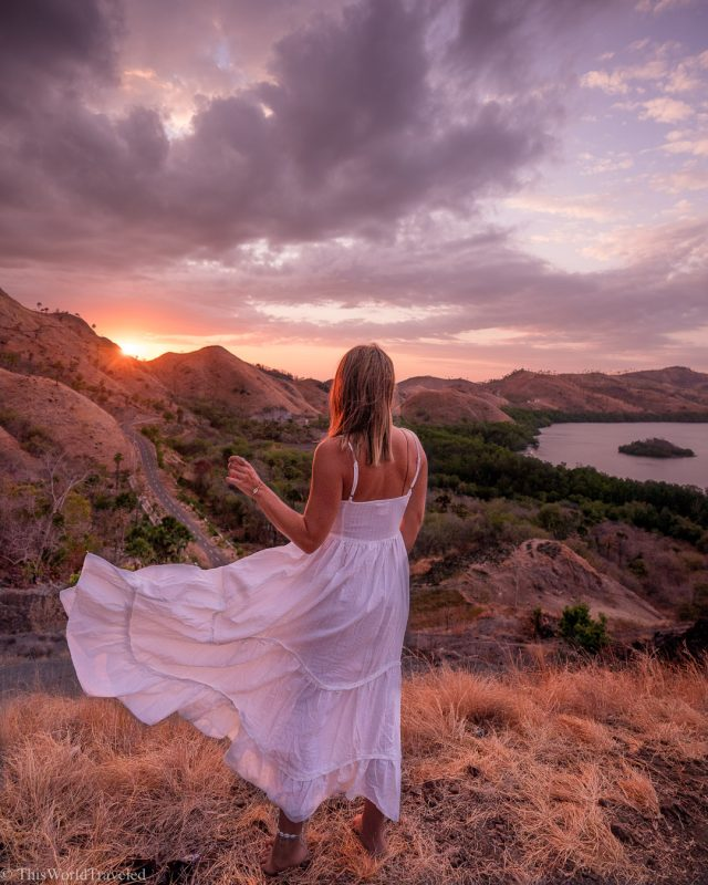 Girl standing at the top of a hill on the island of Flores during sunset