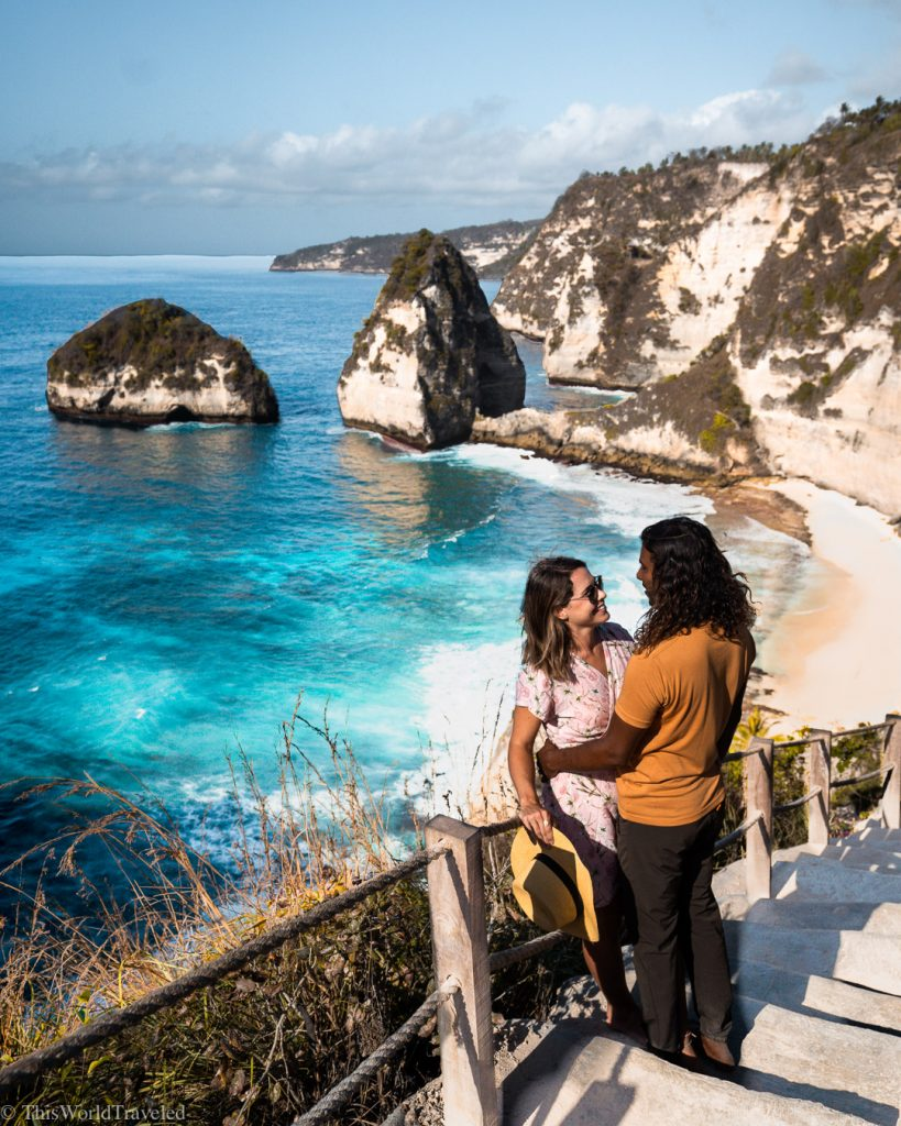 girl and guy standing on stairs with a view of the turquoise waters of diamond beach on nusa penida