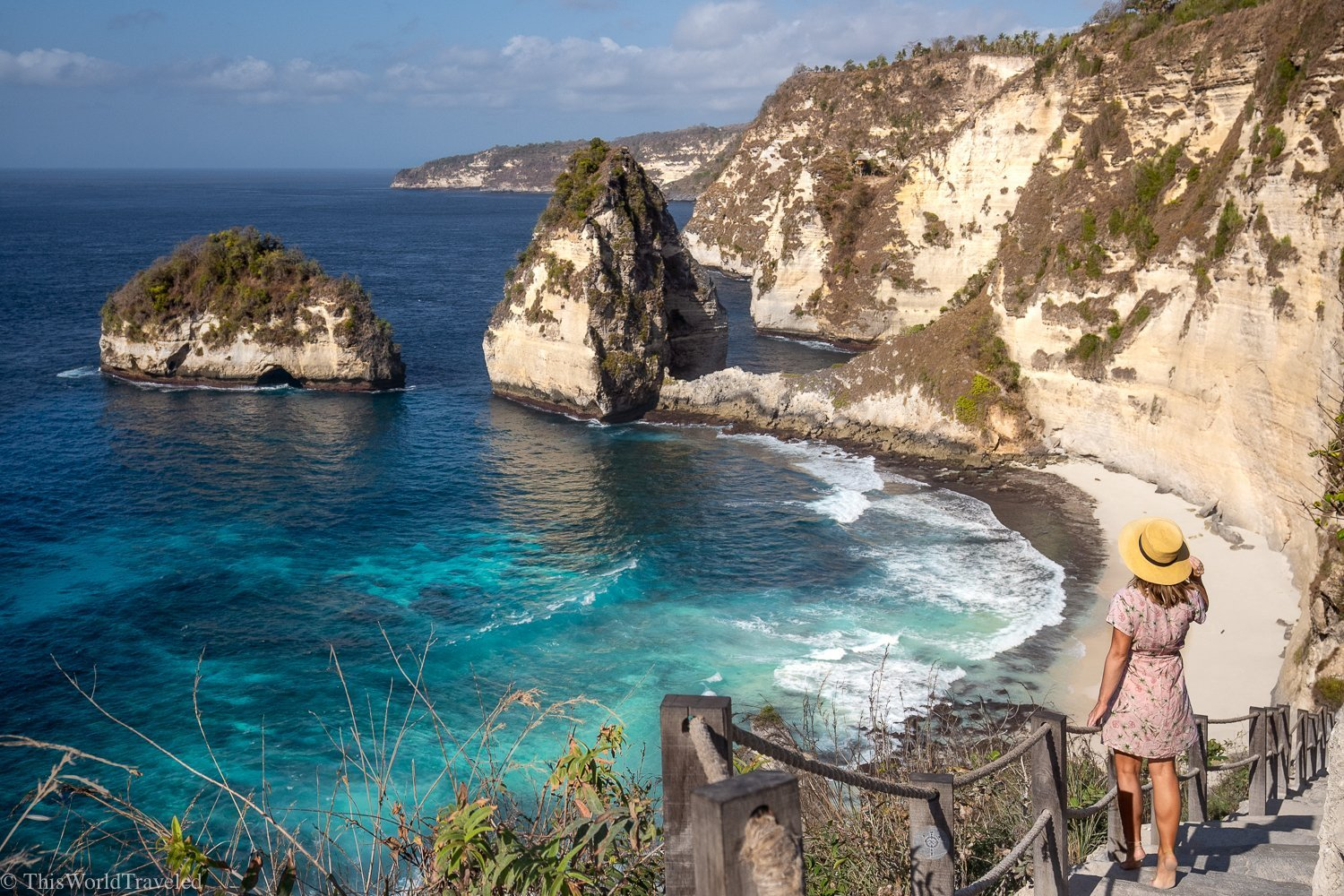 Girl with hat standing on stairs leading down to a beach in Nusa penida