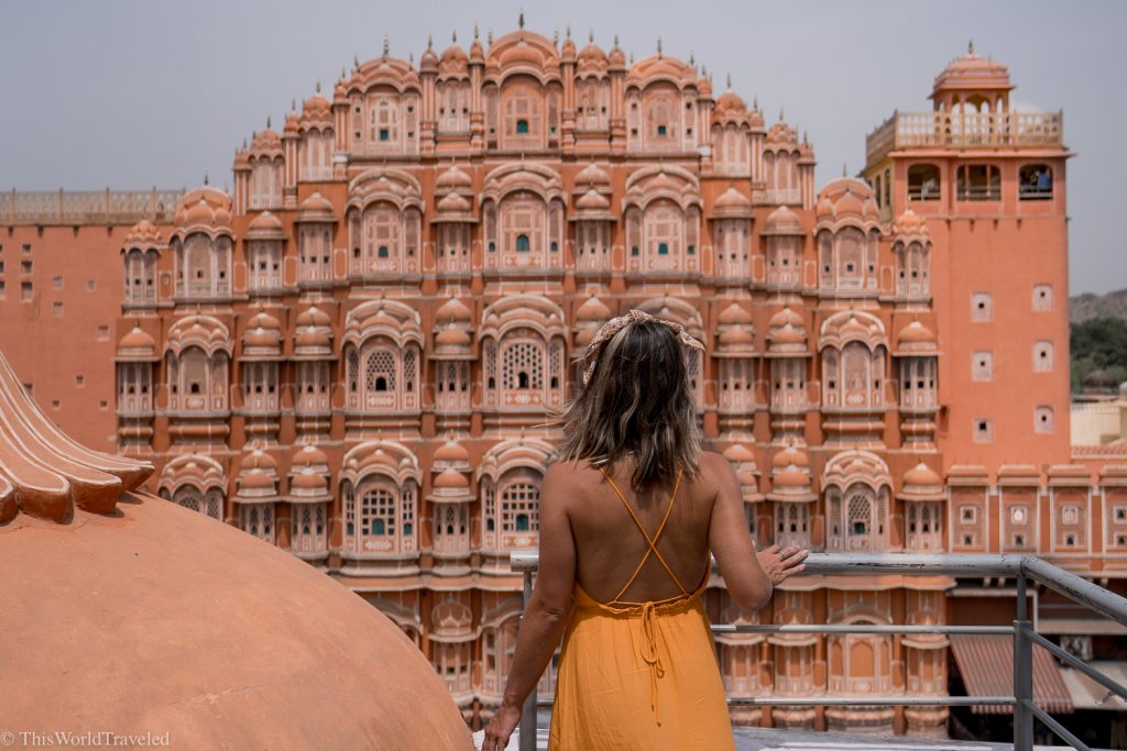 A girl standing in front of the Hawa Mahal in Jaipur, India