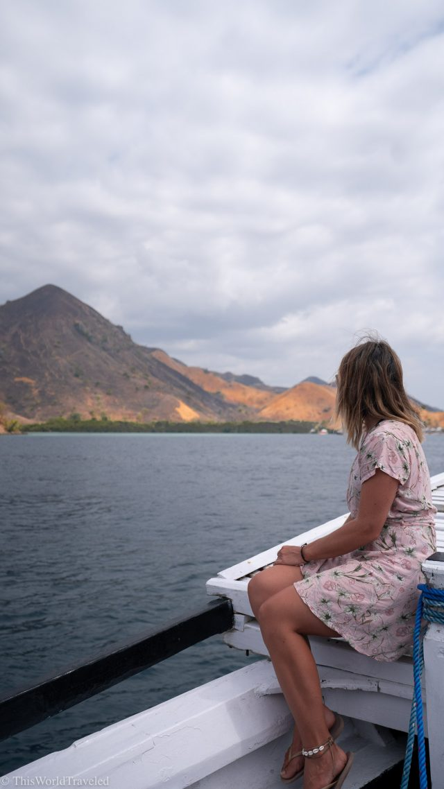 Girl sitting on the edge of a sail boat in the Komodo Islands, Indonesia