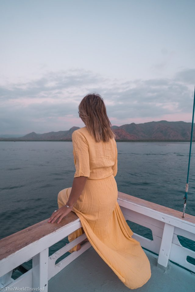 Girl in yellow dress sitting on the edge of a sail boat watching sunset in the Komodo Islands, Indonesia