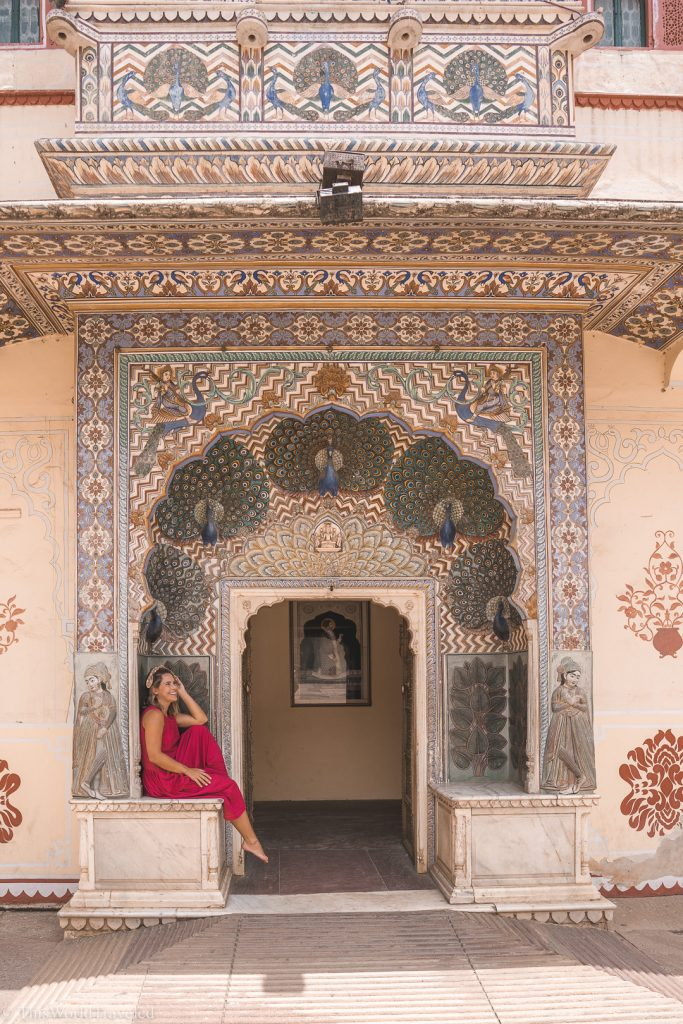 Girl sitting in front of a peacock designed door in Jaipur