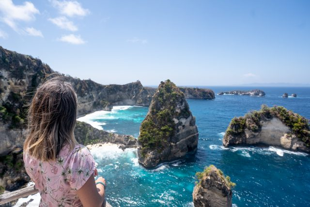 Girl standing in front of a view point of diamond beach on Nusa Penida's east coast