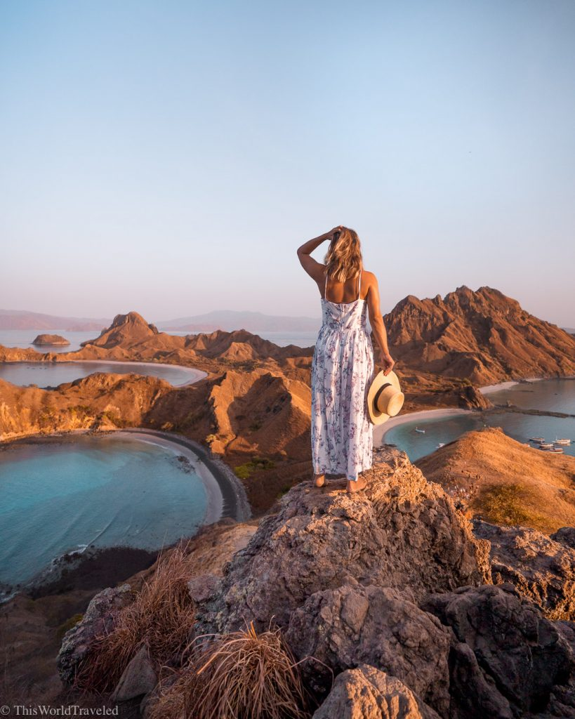 Girl standing on a hill looking over Padar Island in Indonesia