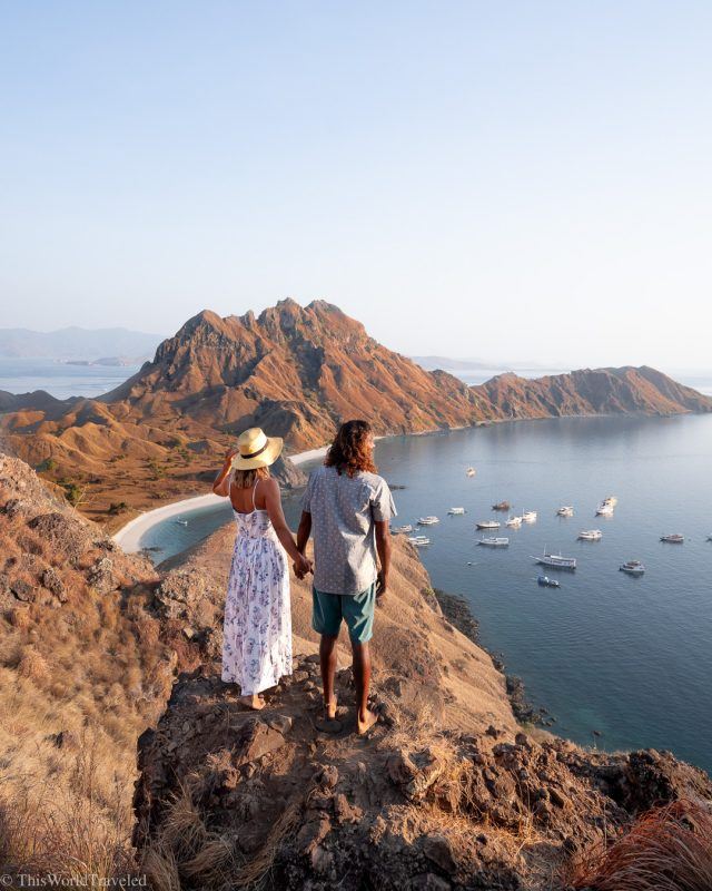 Couple looking out on the ocean while standing at the top of Padar Island in the Komodo Islands