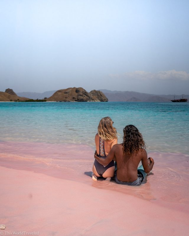 Couple sitting on a pink sand beach in the Komodo Islands, Indonesia