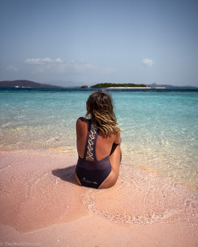 Girl sitting on the pink beach in the Komodo Islands