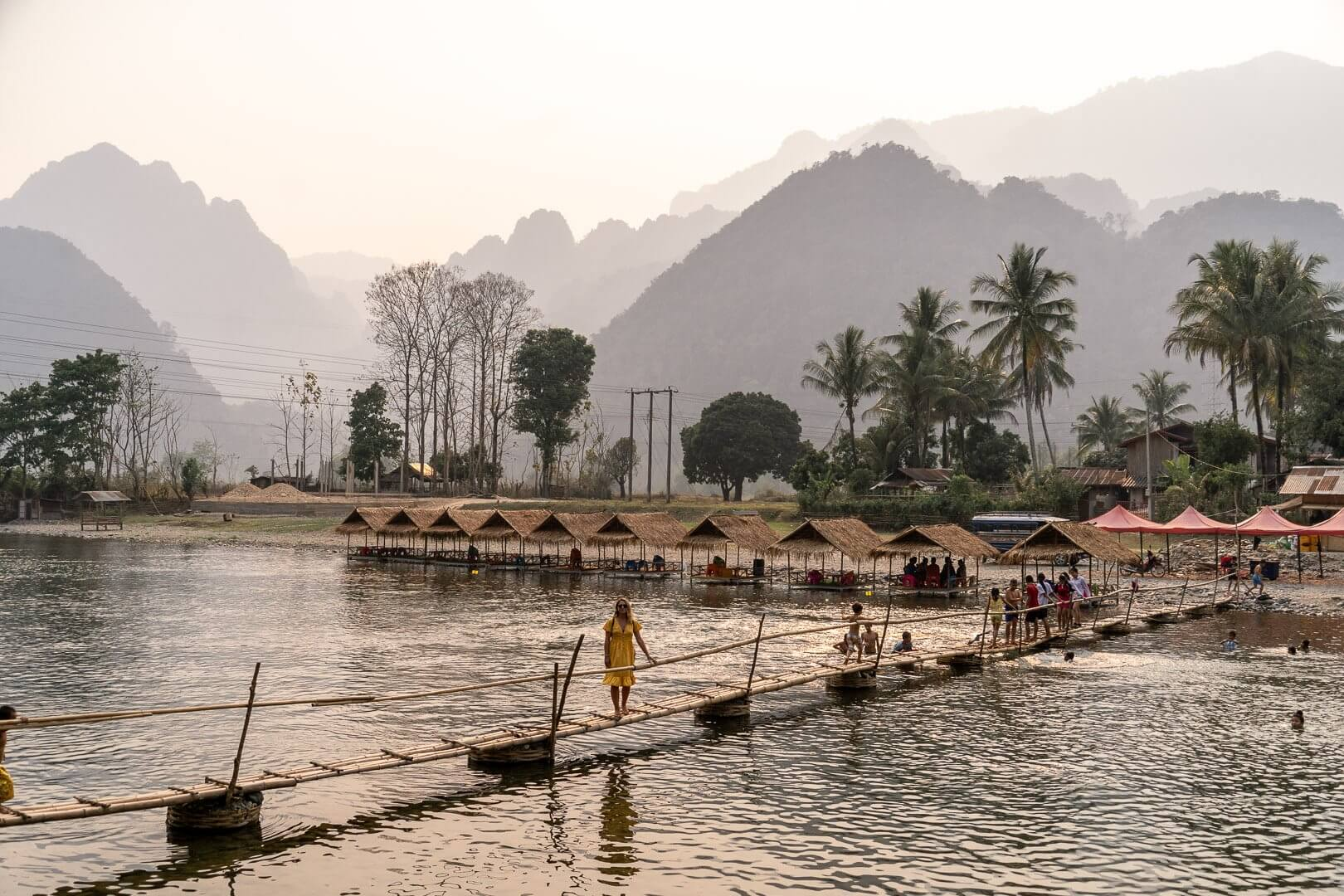 Girl walking across the bamboo bridge in Pha Tang, Laos