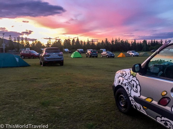 A campsite at sunset in iceland with a camper van parked in the lawn
