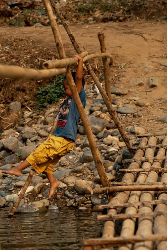Small Laotian boy playing on a bamboo bridge in Pha Tang, Laos