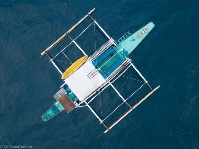 Drone shot of a traditional bamboo boat in the waters of Bacuit Bay near El Nido