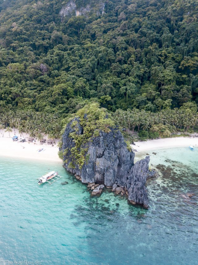 Towering limestone cliffs and sandy beach during an island hopping tour in El Nido