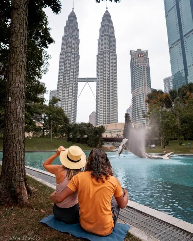Girl and guy sitting in front of the lake and Petronas Twin Towers in Kuala Lumpur, Malaysia