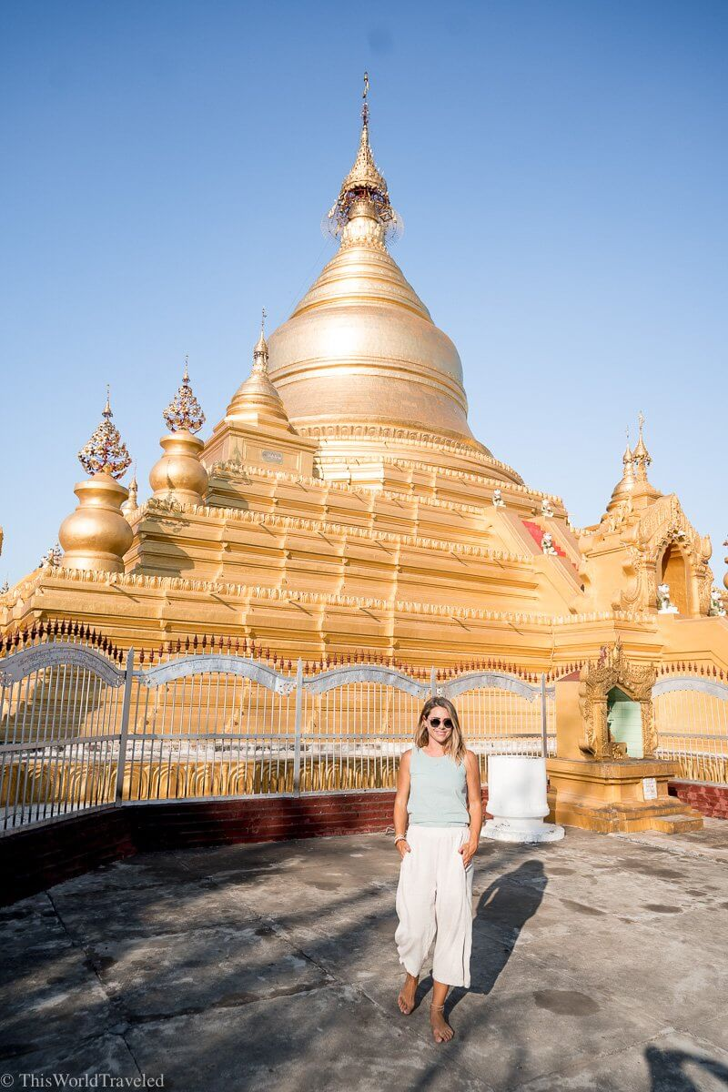 Girl walking in front of the golden stupa at the Kuthodaw Pagoda in Mandalay, Myanmar