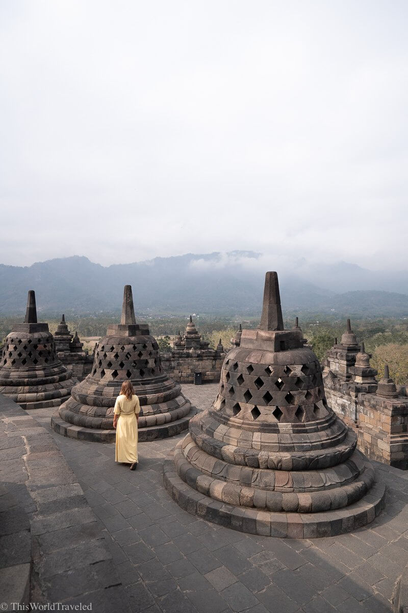 Girl in yellow dress walking around the stupas at the Borobudur Temple in Indonesia