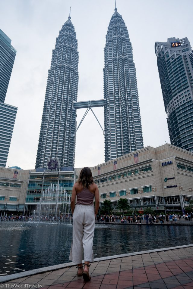 Girl standing in front of the twin towers in KL, Malaysia
