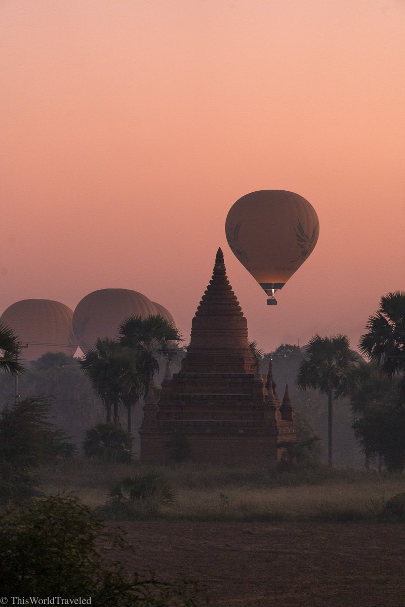 The sun rising and balloons floating above the temples in Bagan, Myanmar