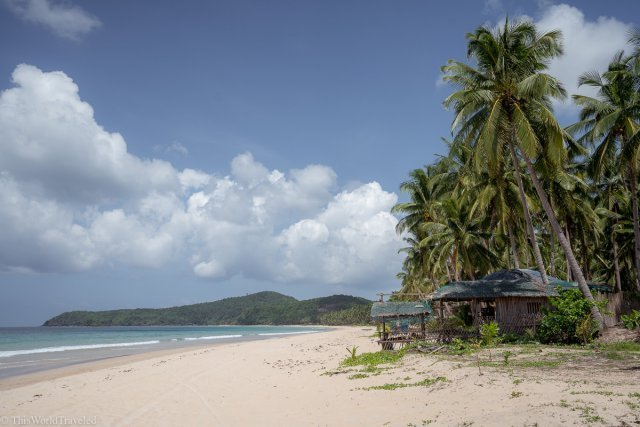 White sandy beach, palm trees and turqouise water at a beach in Palawan
