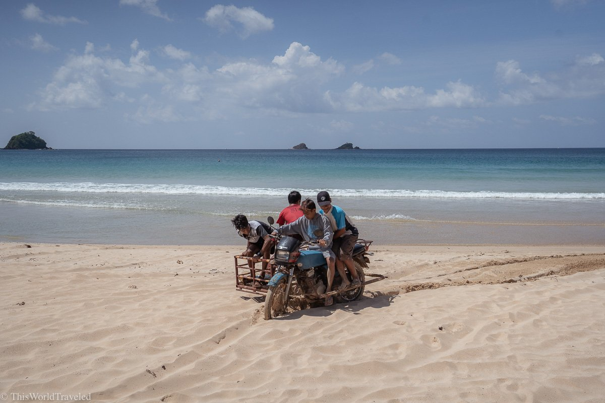 A group of kids driving a tricycle on the beach in El Nido