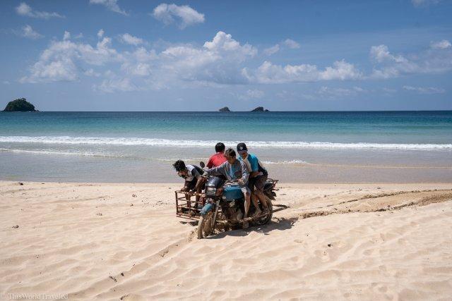 Kids driving their tricycle on Nacpan Beach in El Nido