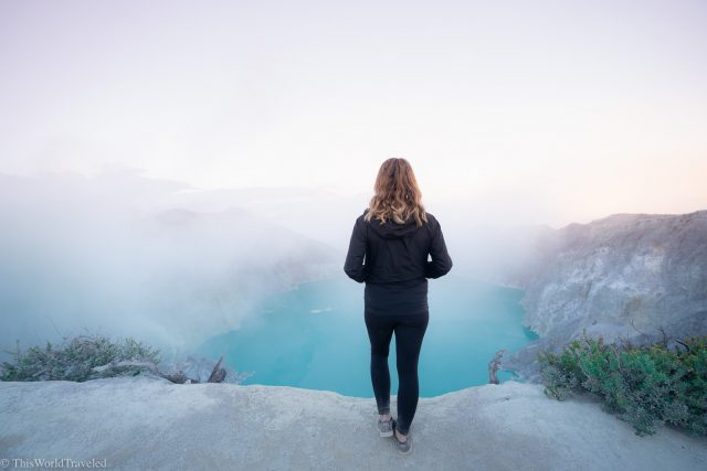 Girl standing in front of the Ijen Crater Lake at sunrise in Java, Indonesia