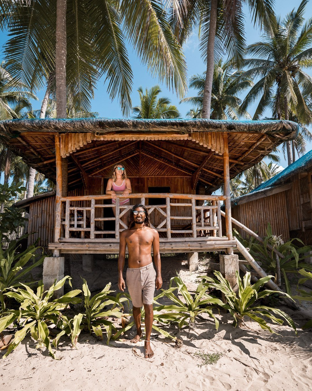 Guy and girl hanging out in a hut on Nacpan Beach in the Philippines