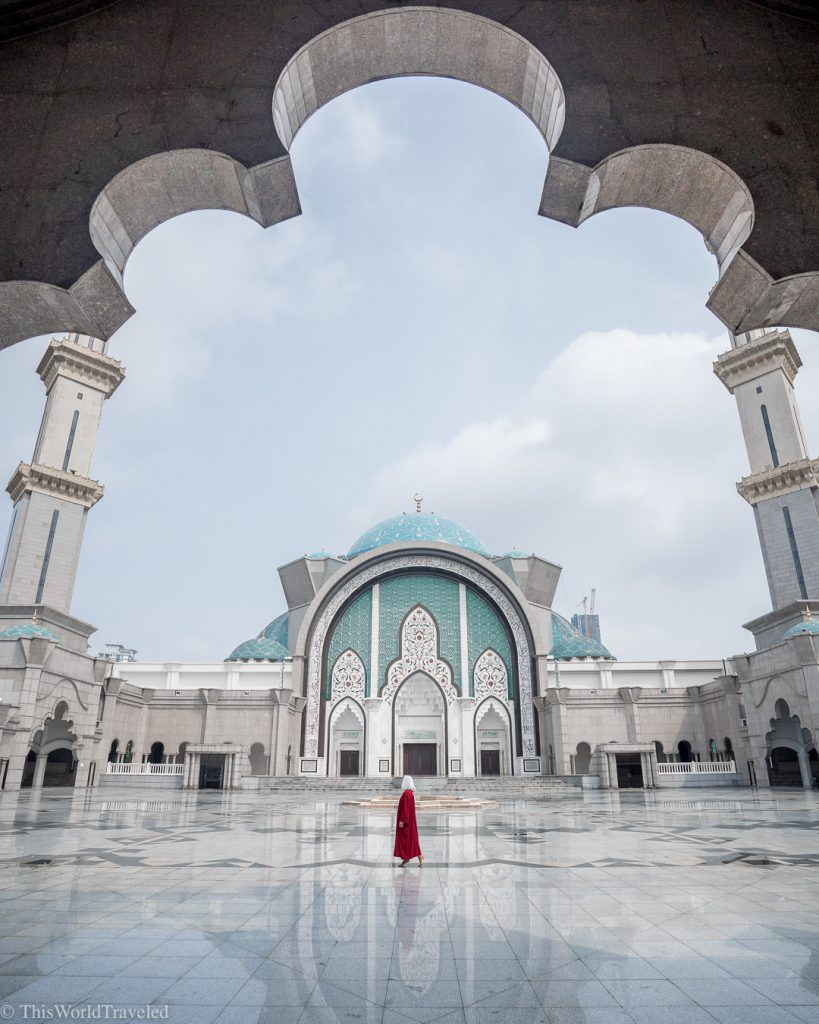 Girl standing in front of the exterior of the Wilayah Mosque in Kuala Lumpur, Malaysia