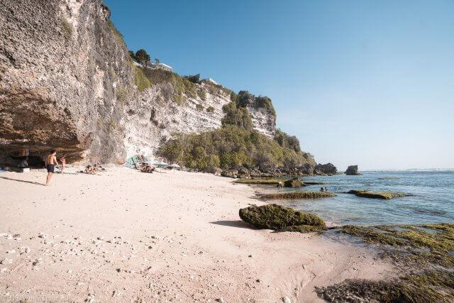The soft white sand and cliff views at the hidden beach near Single Fin in Uluwatu, Bali