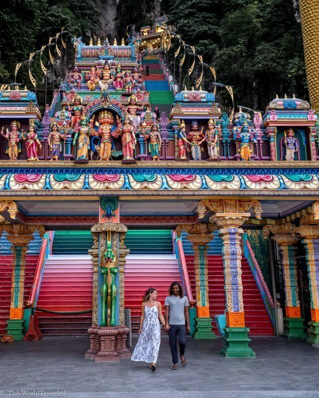 Girl and guy in front of the colorful steps at the Batu Caves in Kuala Lumpur, Malaysia