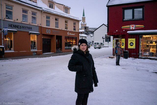 Girl standing in the town of Tromsø, Norway with all her winter hear on!