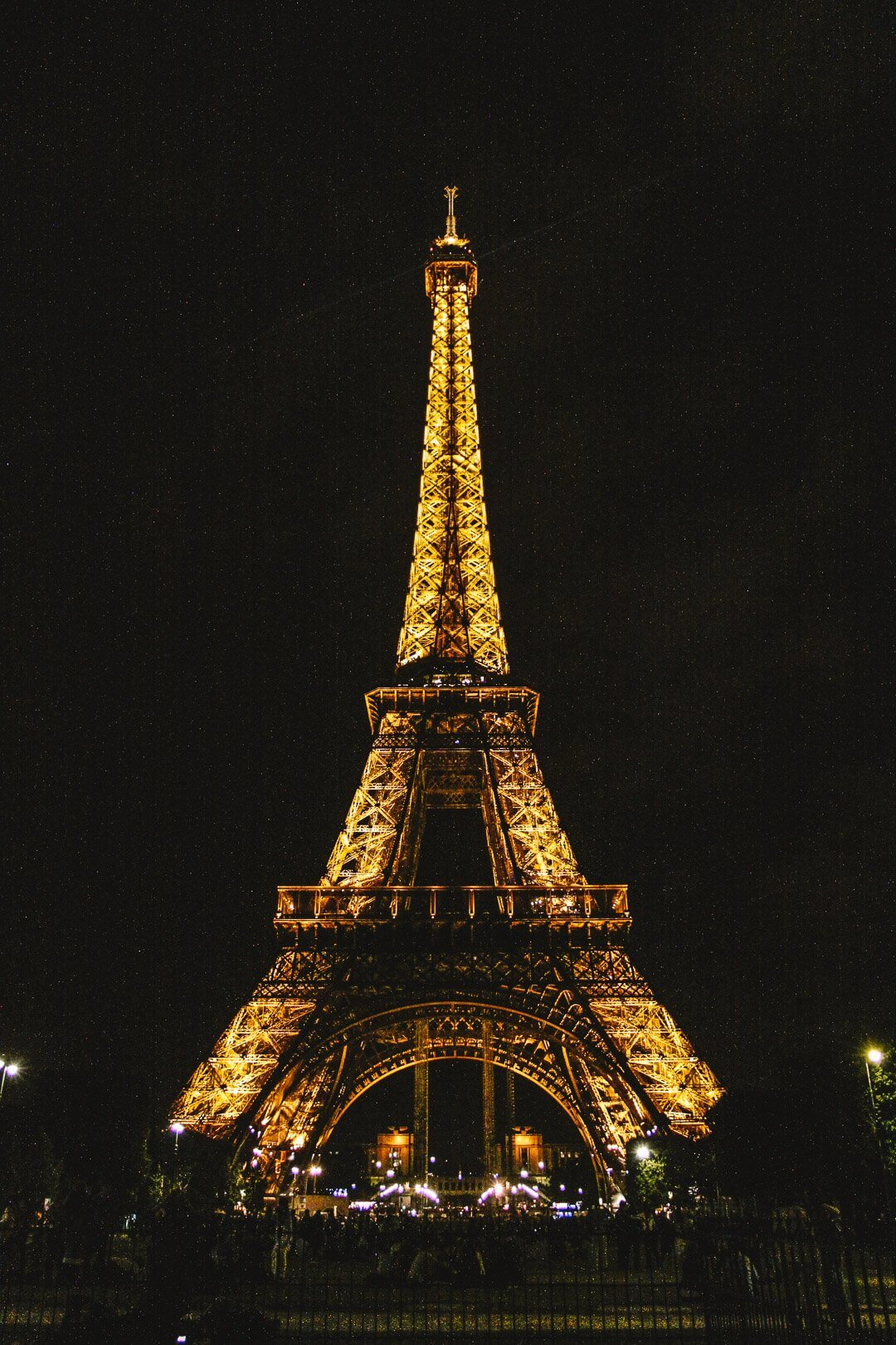 The Eiffel Tower lit up with lights at night in Paris, France