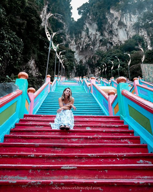 Girl in white dress sitting on the rainbow stairs of the Batu Caves in Kuala Lumpur, Malaysia