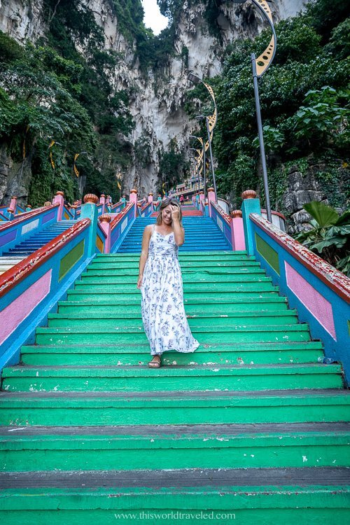 Girl walking on the green steps of the Batu Cave temple in Malaysia