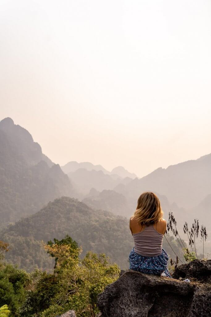 Girl in blue skirt sitting on rocks at the Nam Xay viewpoint in Vang Vieng, Laos