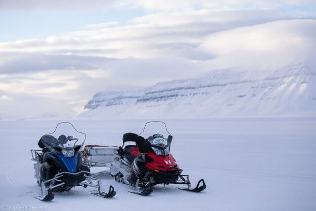 A red and blue snowmobile on the snow covered fjord in Svalbard, Norway