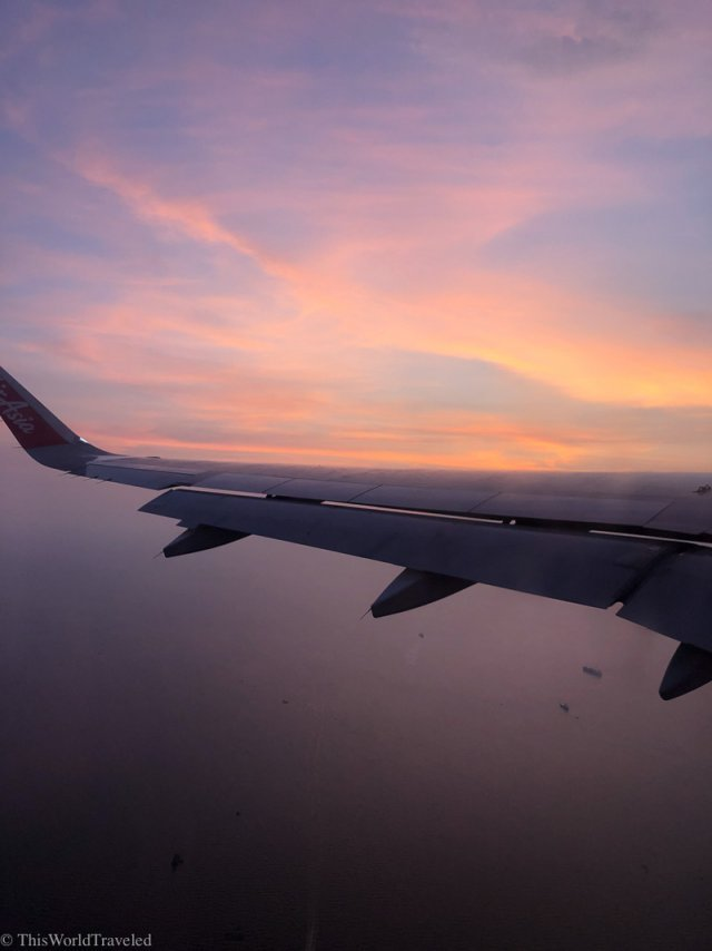 Airplane wing flying in the orange sky during sunset