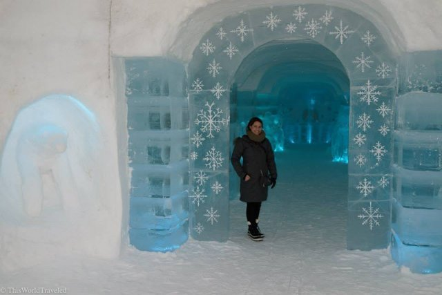 Girl standing in front of the Sorrisniva Igloo Hotel in Northern Norway