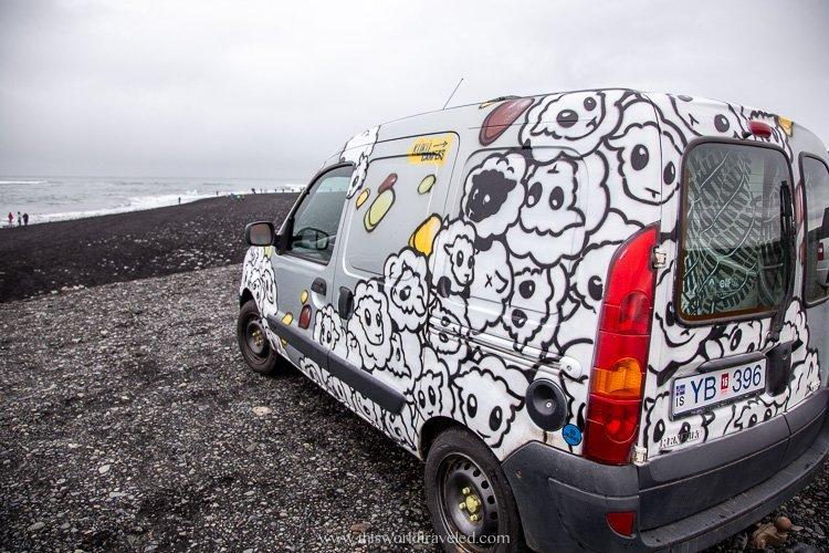 A KuKu Camper van parked along side the black sandy beach in Iceland