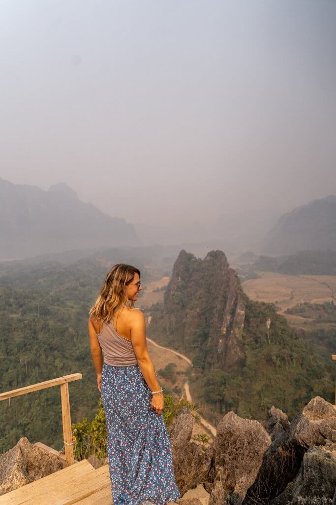 Girl in blue skirt standing on the viewing platform at the Nam Xay hike viewpoint in Vang Vieng