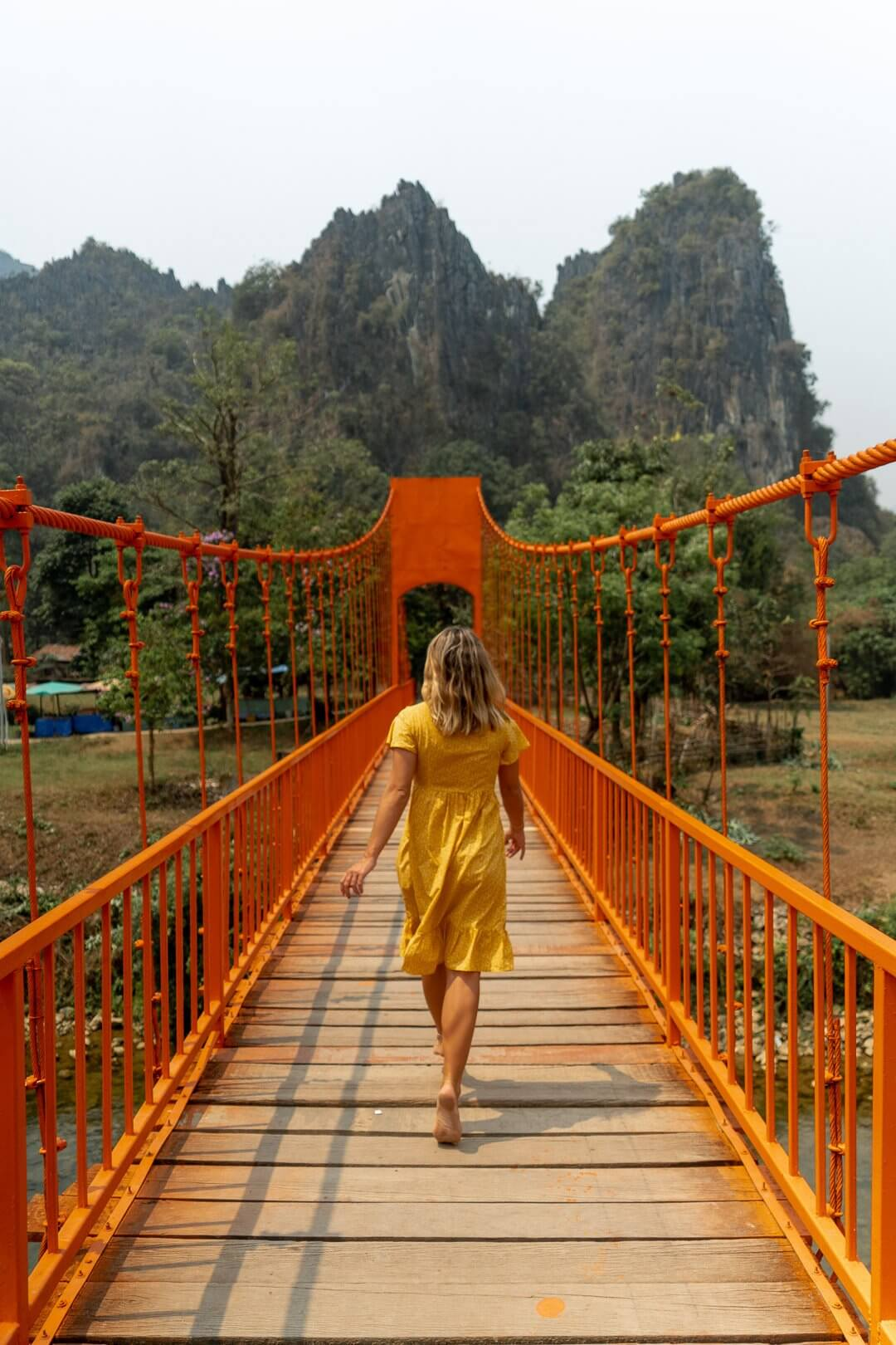 Girl in yellow dress running across an orange bridge in Vang Vieng, Laos