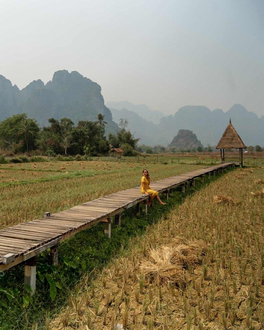 Girl sitting on the wooden boardwalk over the rice terraces in Vang Vieng, Laos