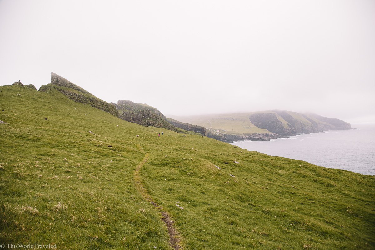 Walking along the ridge in Mykines in the Faroe Islands with views of the cliffs and ocean